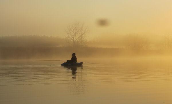 Sunrise over float tube fisherman